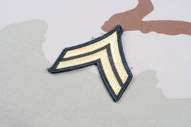 US ARMY Corporal rank patch on desert uniform. Background royalty free stock photography
