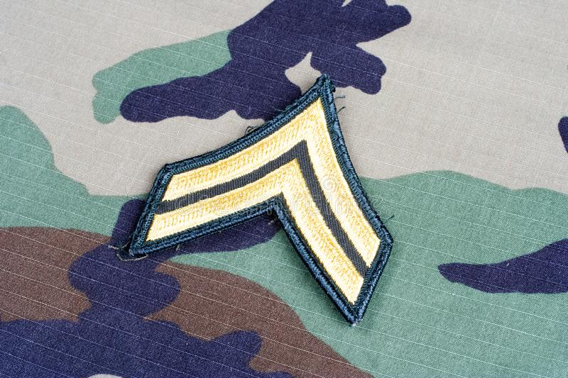 US ARMY Corporal rank patch on woodland camouflage uniform. Background stock photo