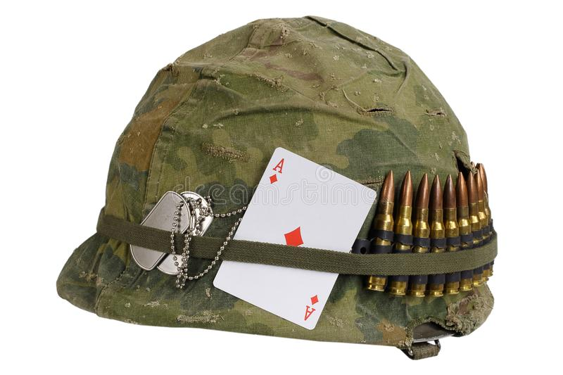 US Army helmet Vietnam war period with camouflage cover and ammo belt, dog tag and amulet playing card ace of diamonds. US Army helmet Vietnam war period with stock images