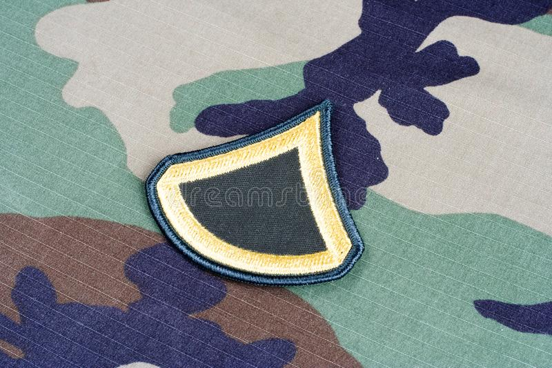 US ARMY Private First Class rank patch on woodland camouflage uniform. Background stock photos