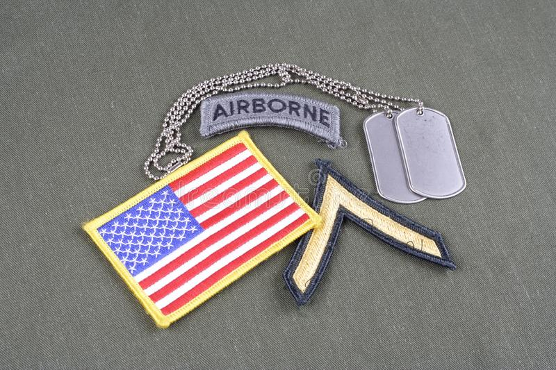 US ARMY Private rank patch, airborne tab, flag patch and dog tag on olive green uniform. Background royalty free stock photography