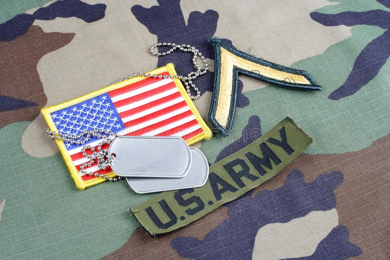 US ARMY Private rank patch, branch tape, flag patch and dog tags on woodland camouflage uniform. Background royalty free stock photography