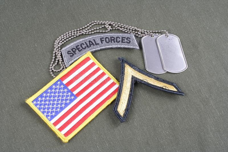 US ARMY Private rank patch, special forces tab, flag patch and dog tag on olive green uniform. Background royalty free stock photo