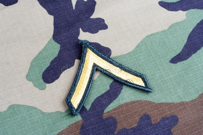 US ARMY Private rank patch on woodland camouflage uniform. Background stock image
