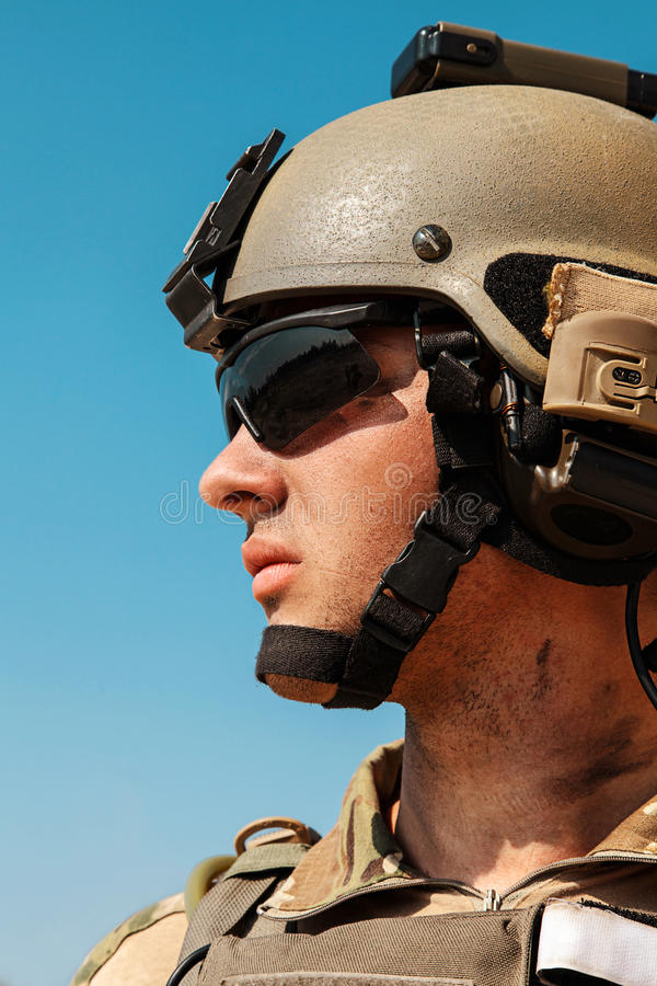 US Army Ranger in the desert beneath a scorching sun. US Army Ranger with weapons in the desert beneath a scorching sun. Closeup face portrait. He is wearing stock photography