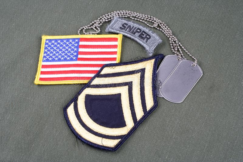 US ARMY Sergeant First Class rank patch, sniper tab, flag patch and dog tag on olive green unifo. Rm stock photos