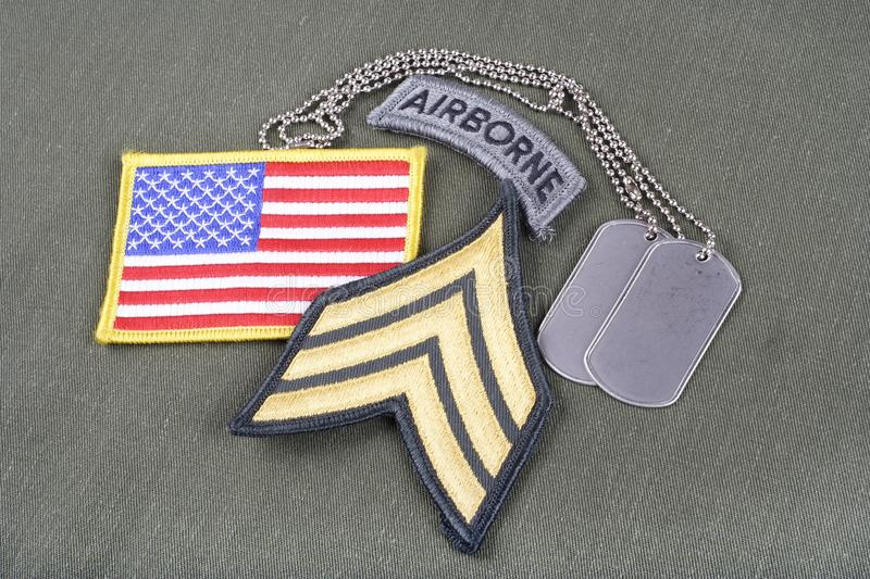 US ARMY Sergeant rank patch, airborne tab, flag patch and dog tag on olive green uniform. Background stock photos
