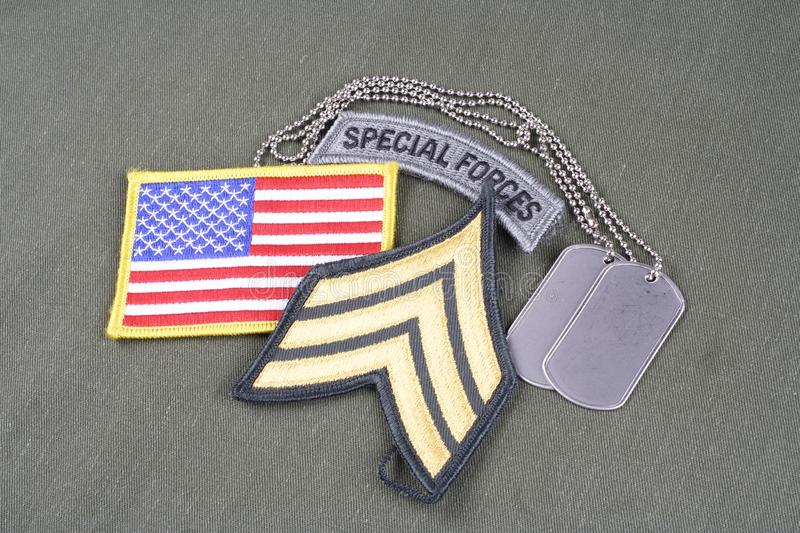 US ARMY Sergeant rank patch, special forces tab, flag patch and dog tag on olive green uniform. Background stock image