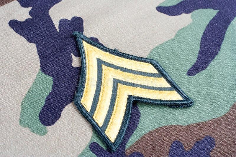 US ARMY Sergeant rank patch on woodland camouflage uniform. Background stock photo