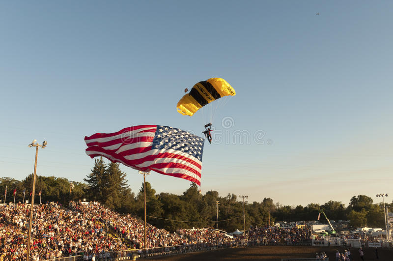 US Army Skydiver with US Flag. Folsom, CA, USA - July 4, 2010: US Army Skydiver with US Flag landing at Folsom rodeo stock images