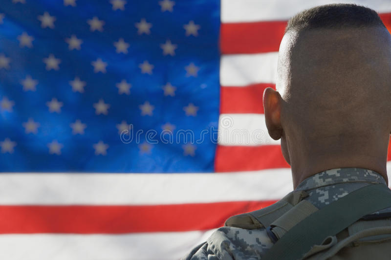 US Army Soldier Looking At Flag. Rear view of US army soldier looking at the American flag stock photography