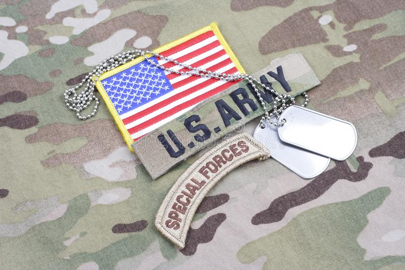 US ARMY special forces tab, flag patch, with dog tag on camouflage uniform stock photography