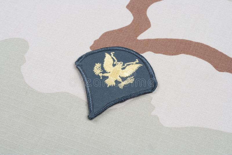 US ARMY Specialist rank patch on desert uniform. Background royalty free stock images