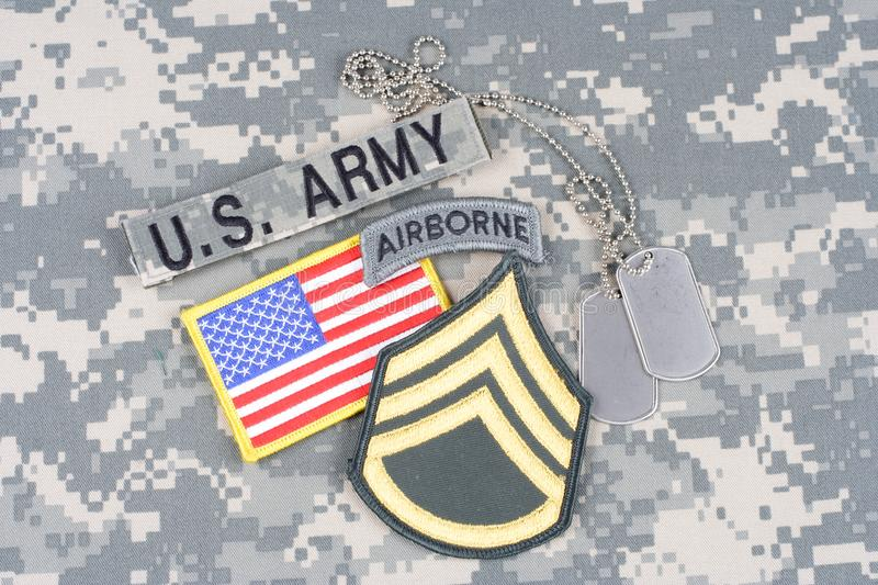 US ARMY Staff Sergeant rank patch, airborne tab, flag patch, with dog tag on camouflage uniform royalty free stock photos