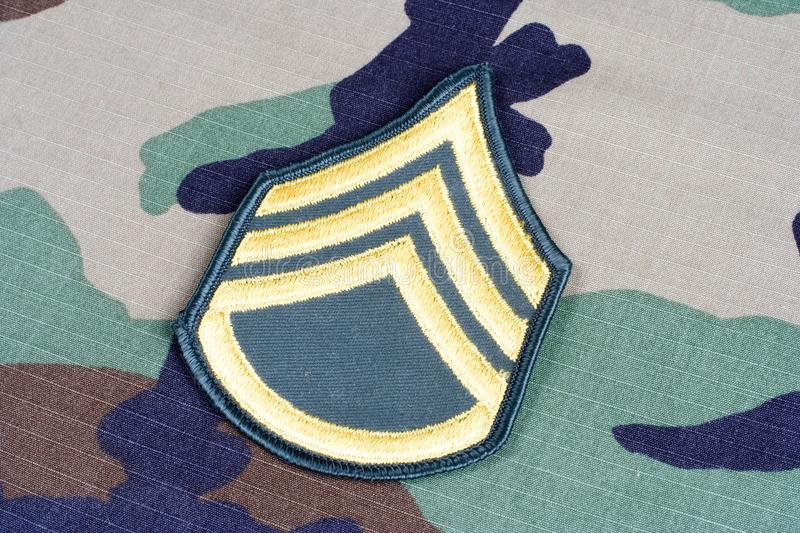 US ARMY Staff Sergeant rank patch on woodland camouflage uniform. Background stock images