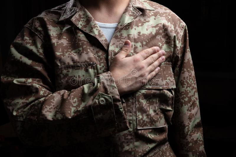 Young soldier with hand on heart standing on black background stock photo