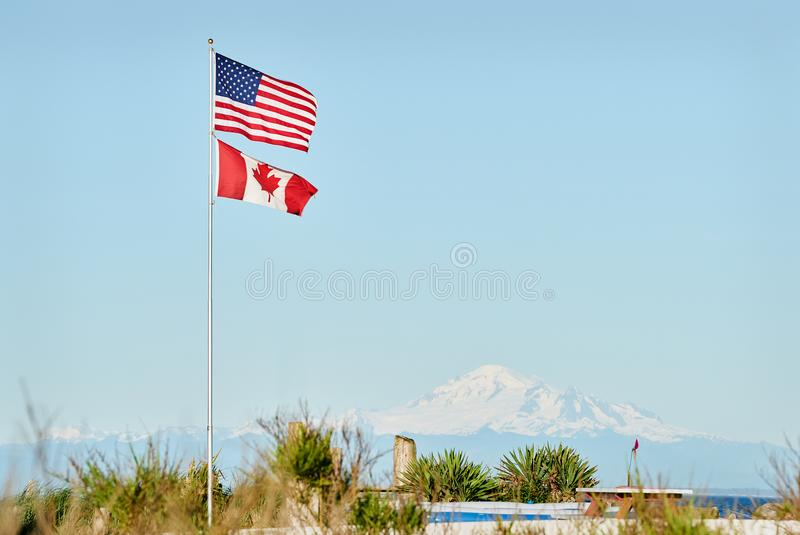 US and Canadian Flag. S fly in Point Roberts, Washington State. Mt Baker in the background royalty free stock photo