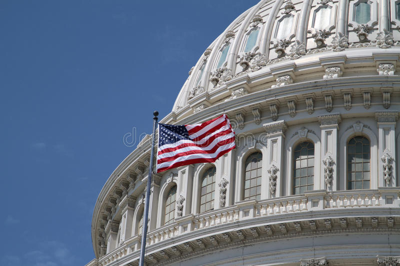 US Capitol and american flag. The dome of the US United States Capitol building for Democrat Republican Government Senate and House congress parties under a stock image