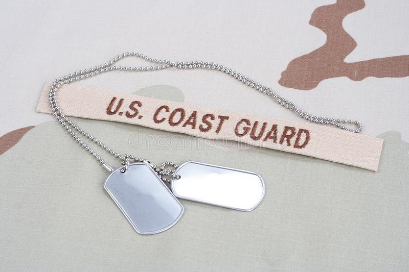 US COAST GUARD branch tape with dog tags on desert camouflage uniform. Background royalty free stock photos