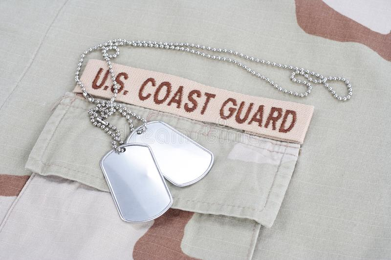 US COAST GUARD branch tape with dog tags on desert camouflage uniform. Background royalty free stock image