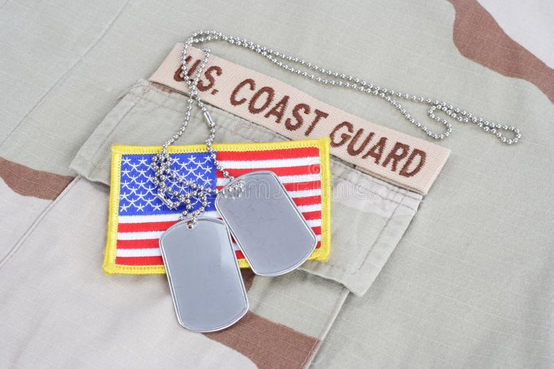 US COAST GUARD branch tape with dog tags and flag patch on desert uniform. US COAST GUARD branch tape with dog tags and flag patch on desert camouflage uniform royalty free stock photo