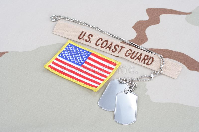 US COAST GUARD branch tape with dog tags and flag patch on desert uniform. US COAST GUARD branch tape with dog tags and flag patch on desert camouflage uniform royalty free stock images