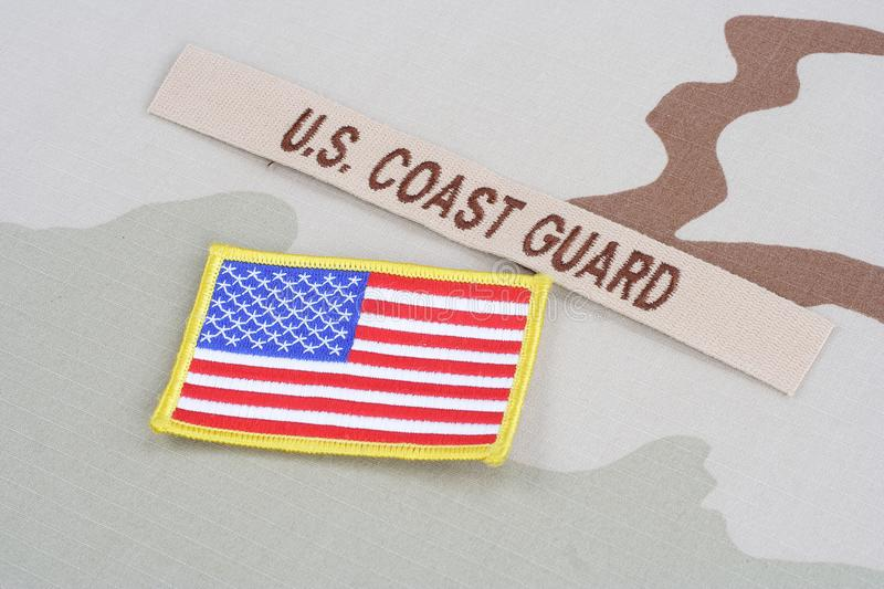 US COAST GUARD branch tape with flag on desert camouflage uniform. Background royalty free stock image