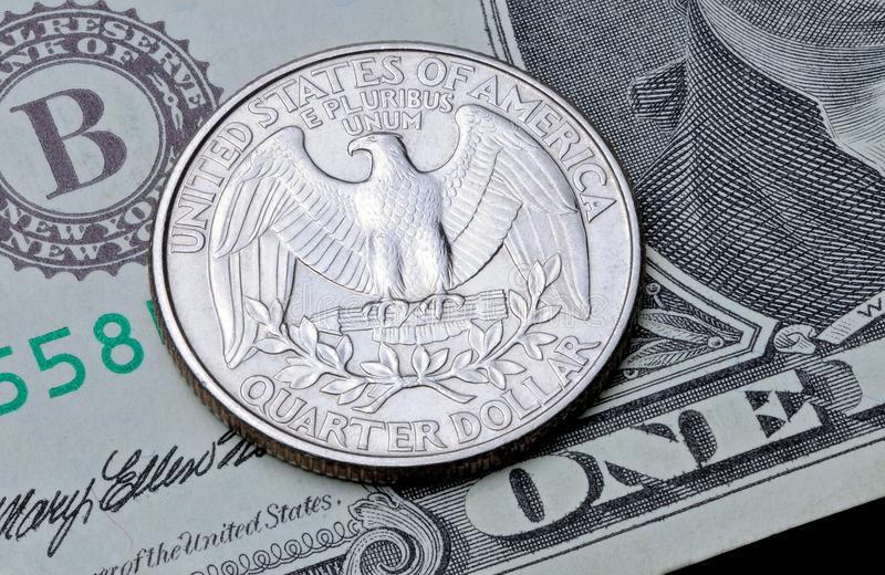US coin quarter dollar on one dollar bill. stock images