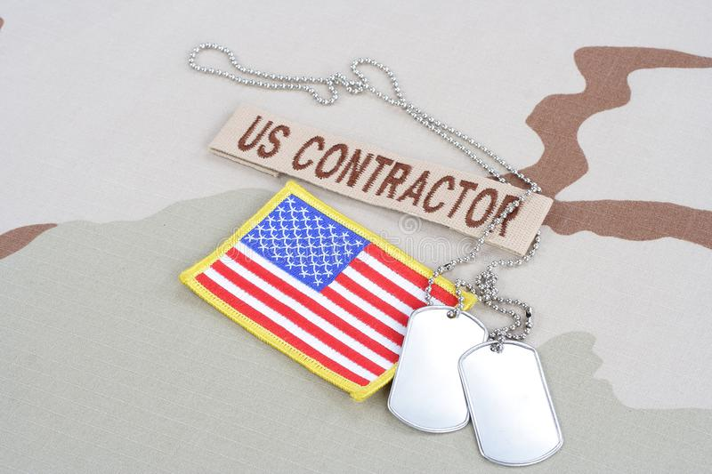 US CONTRACTOR branch tape with dog tags and flag patch on desert camouflage uniform. Background stock image