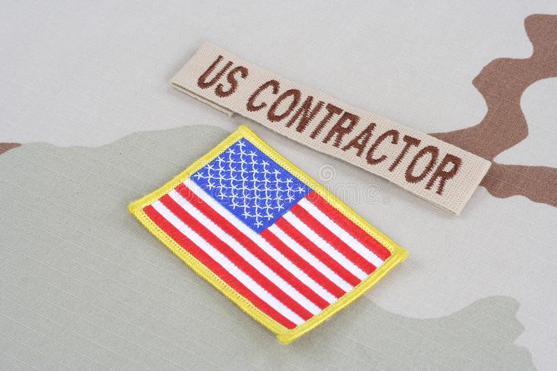 US CONTRACTOR branch tape and flag patch on desert camouflage uniform. Background royalty free stock image
