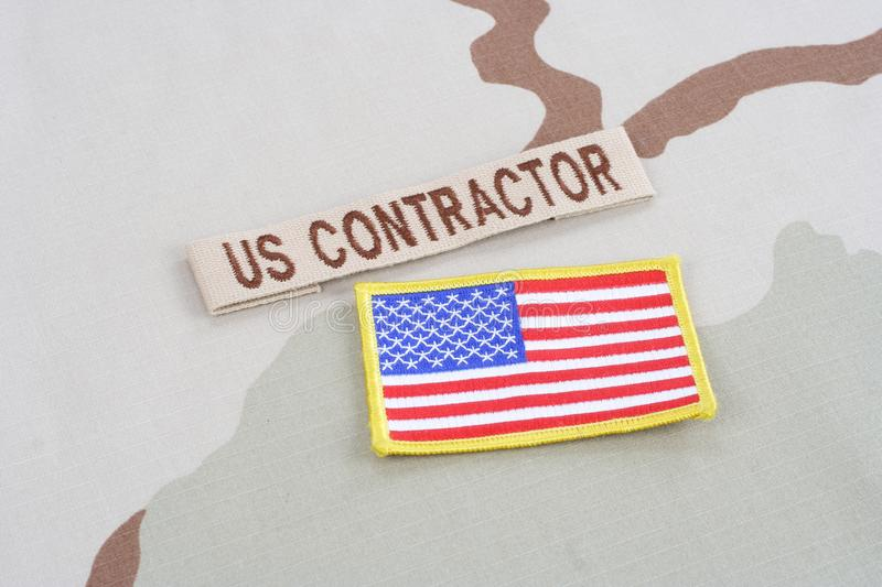 US CONTRACTOR branch tape and flag patch on desert camouflage uniform. Background royalty free stock photos