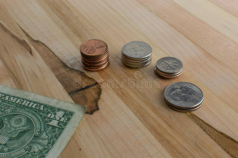 US Currency Cents in Stacks and Dollar Bill on Wooden Table. US pocket change arranged in small stacks along with a folded dollar bill placed on a wooden table stock photography