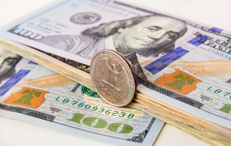 US Currency with one quarter coin. Sitting on one hundred dollar note stock image