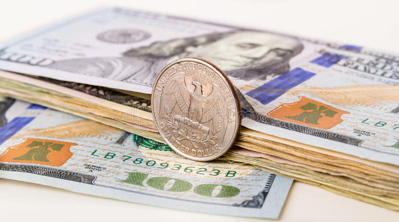 US Currency with one quarter coin. Sitting on one hundred dollar note stock photo