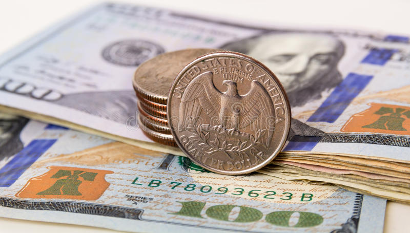 US Currency with one quarter coins. Sitting on one hundred dollar note royalty free stock images