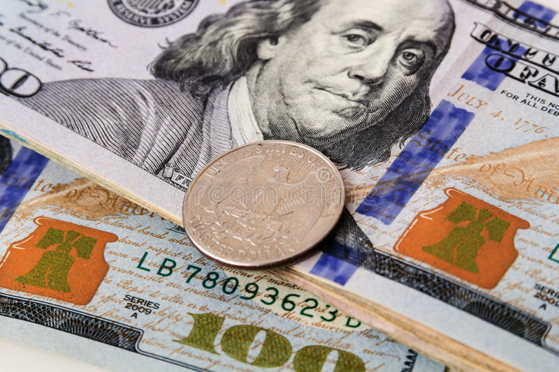 US Currency with one quarter coins. Sitting on one hundred dollar note stock images