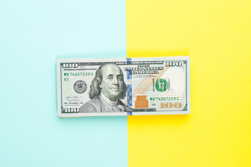 100 US dollar bill money cash on blue and yellow background. Heap of hundred American Dollars banknote.  royalty free stock images