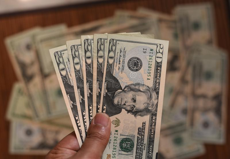 US Dollar bills in human hand with other dollars around in soft focus royalty free stock photos