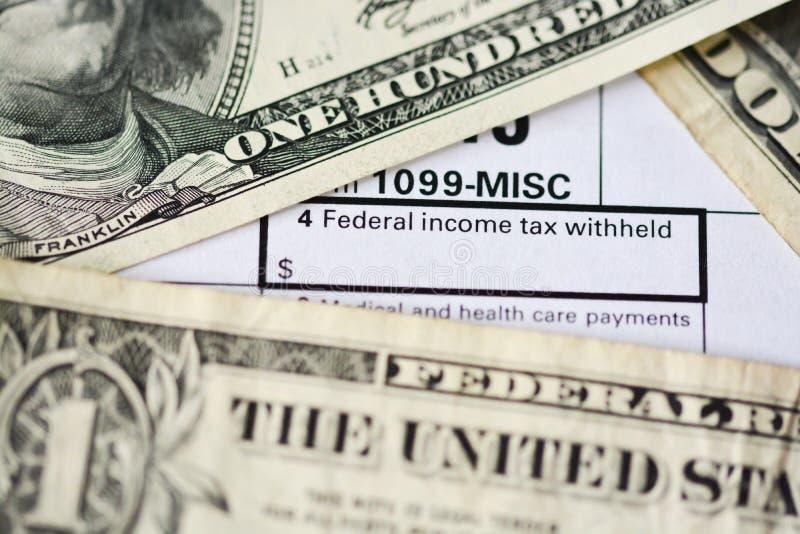 US dollar bills on tax form suggesting tax payment stock photo