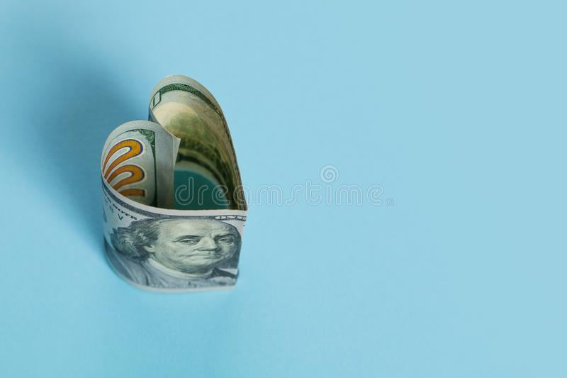US dollar cash money banknote heart shape on blue background, loan and commercial money investment profit concept.  royalty free stock image