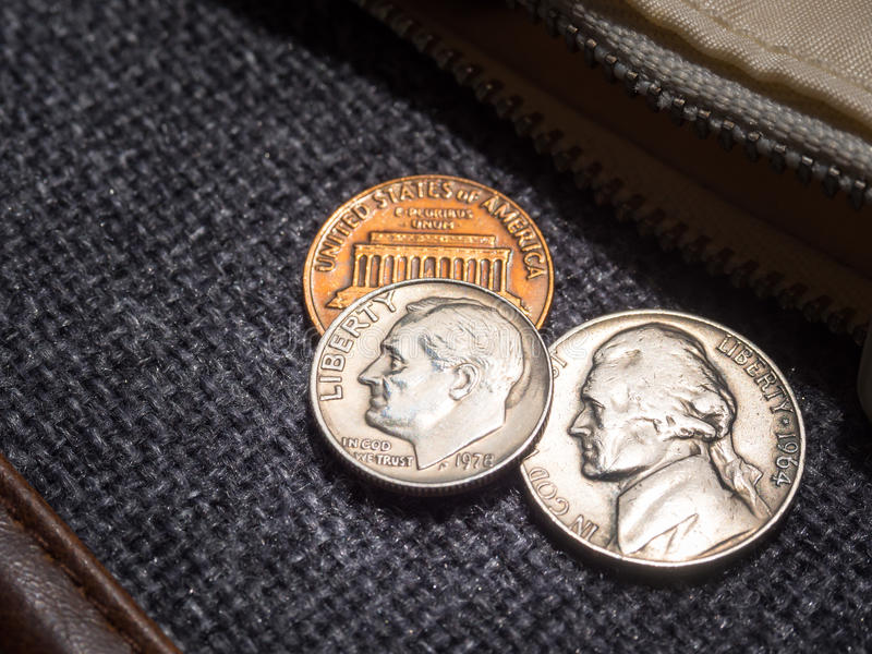 US dollar coins placed outside the wallet.  stock image
