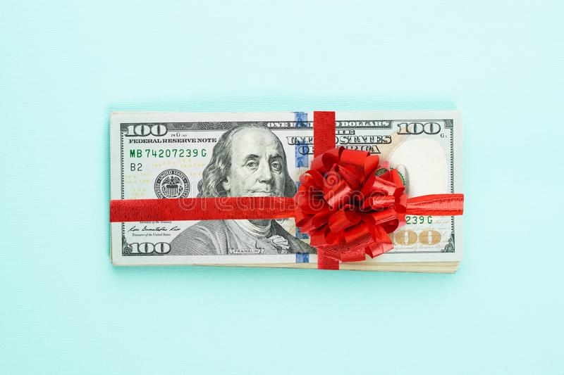 US dollar money cash stack with red ribbon and bow on blue background. American Dollars 100 banknote gift profit concept.  royalty free stock photos