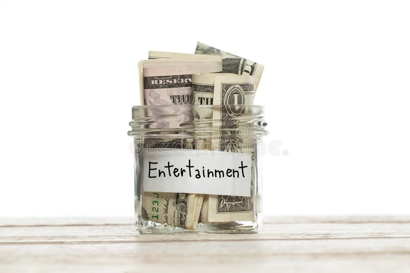 US dollar money for entertainment in saving glass jar on wooden table against white background stock photography