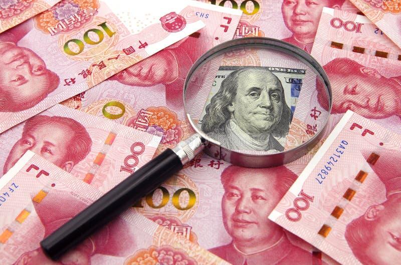 US dollar mot porslinyuan med en förstoringsapparat royaltyfri bild