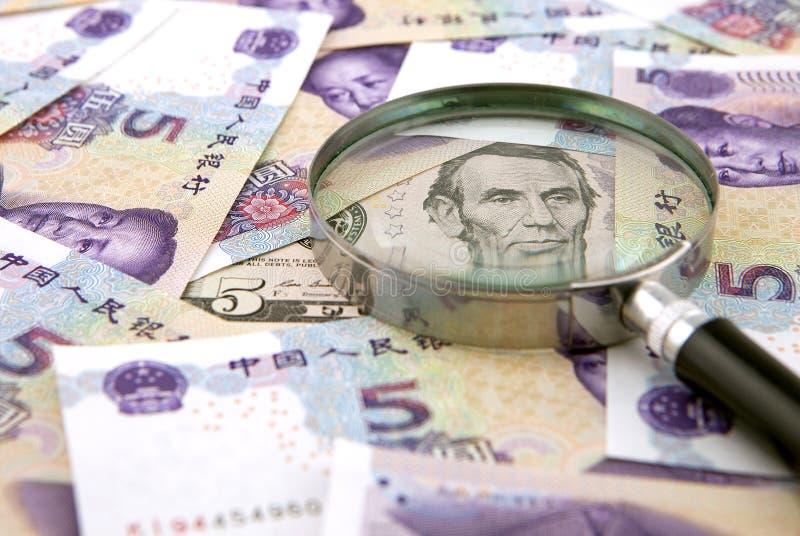 US dollar mot porslinyuan och en förstoringsapparat royaltyfri fotografi