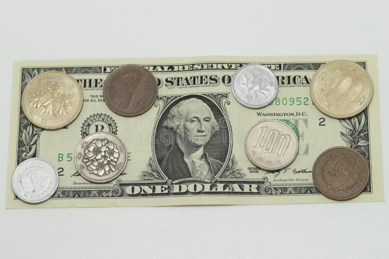 US dollar- och JPN-yenmynt arkivfoto