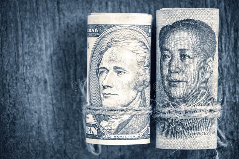 US dollar versus china yuan banknote on the wooden table background. The concept of business growth, financial or trade war royalty free stock photo