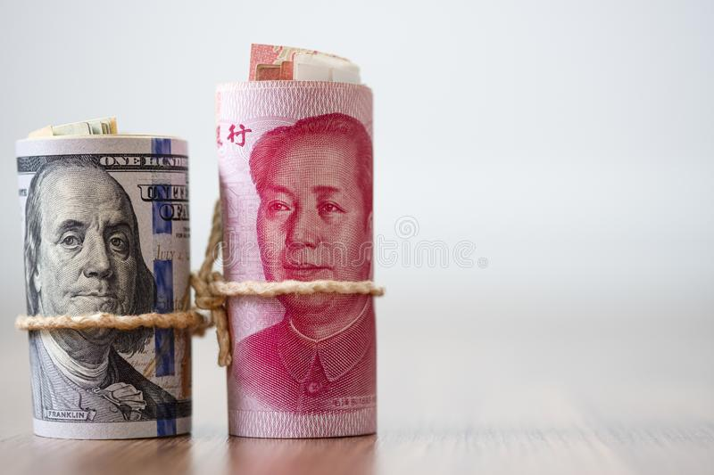 US dollar and Yuan banknote on wooden table. Its is symbol for tariff trade war crisis between United States of America and China. Which the biggest economic stock images