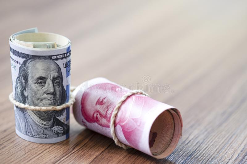 US dollar and Yuan banknote on wooden table. Its is symbol for tariff trade war crisis between United States of America and China. Which the biggest economic stock photo