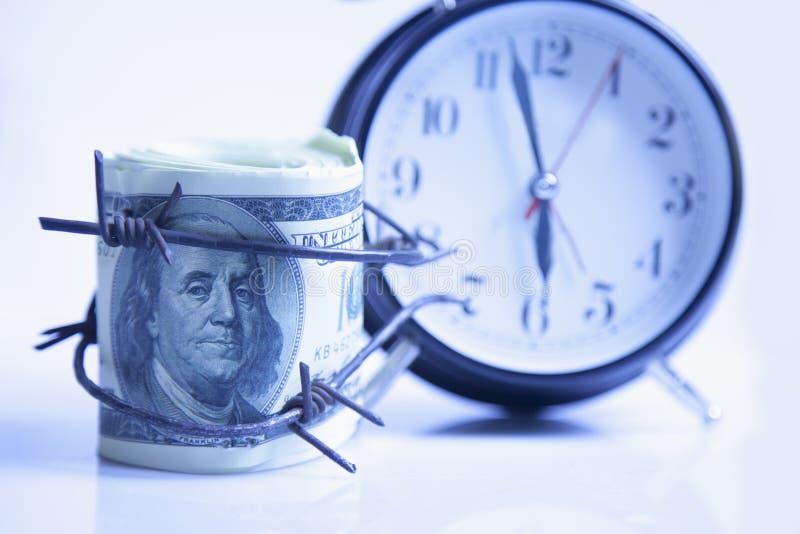 US dollarpengar som slås in i taggtråd mot klockabakgrund fotografering för bildbyråer